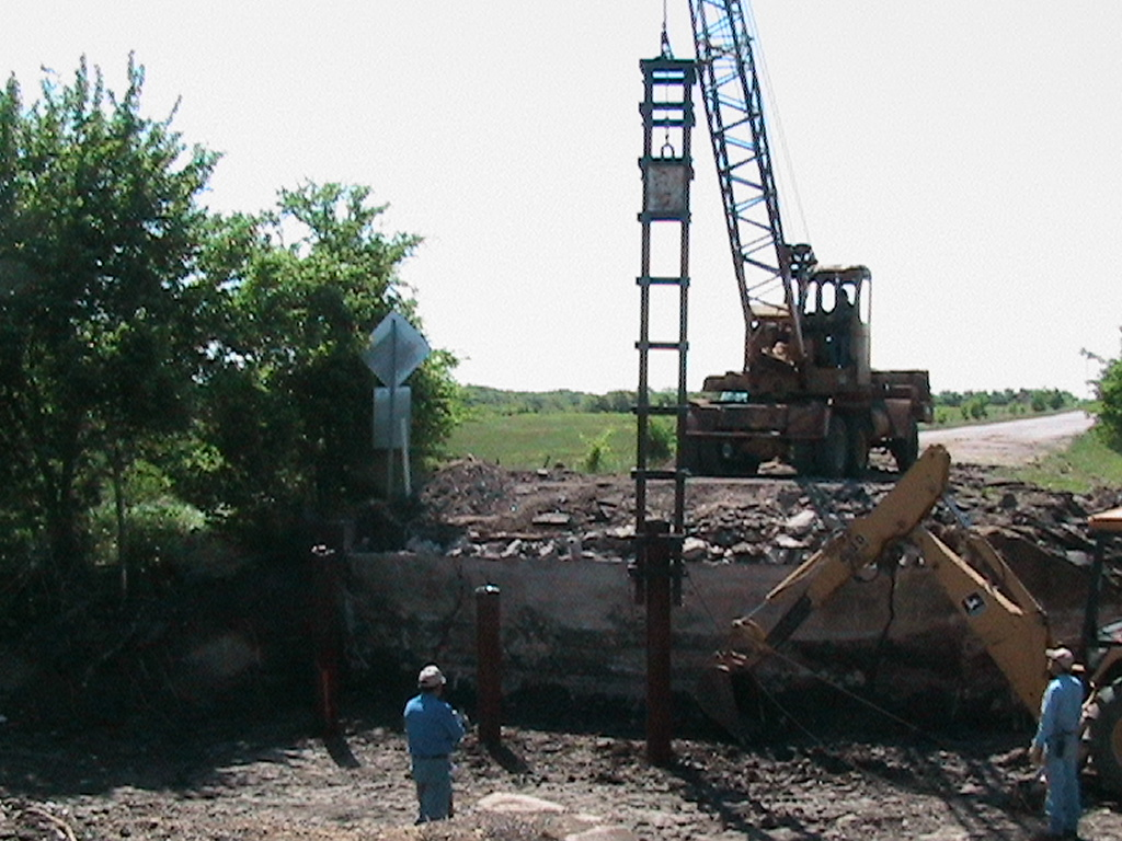 Crain lowering posts into the ground